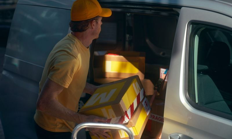 A delivery man loading parcels onto a Caddy Cargo