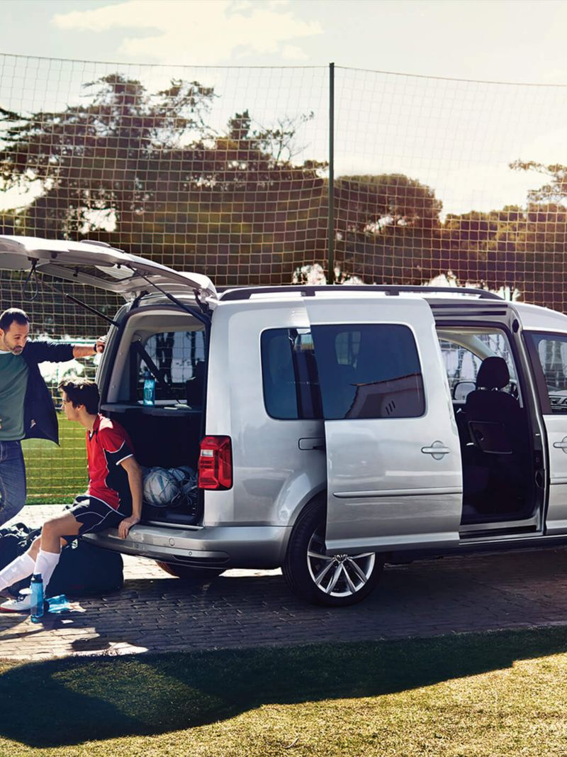family outside VW Caddy Life at football pitch
