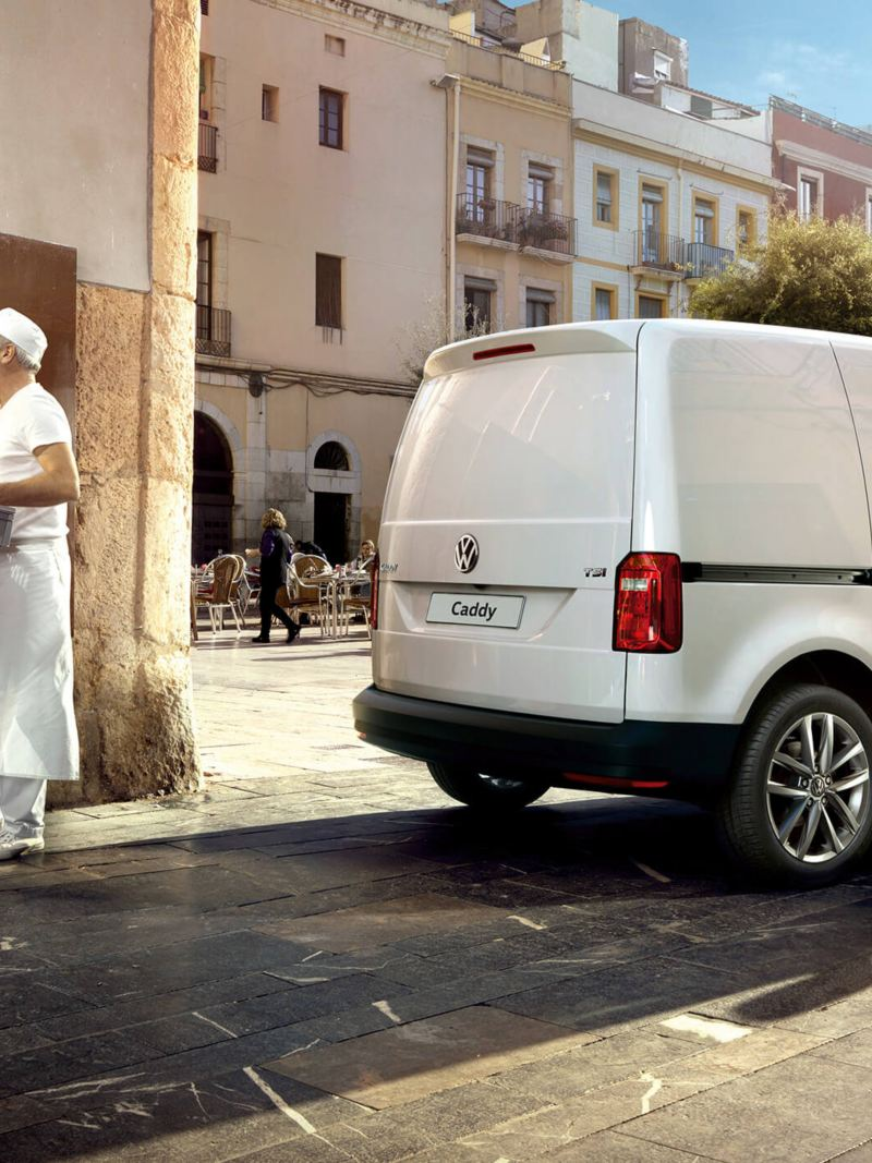 Chefs loading food into Caddy panel van outside bakery