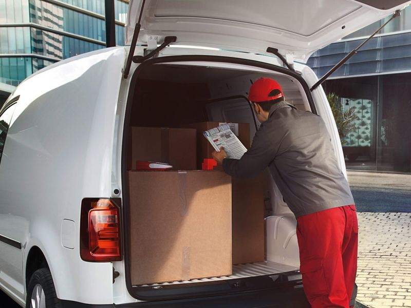 Man loading Caddy panel van through rear tailgate