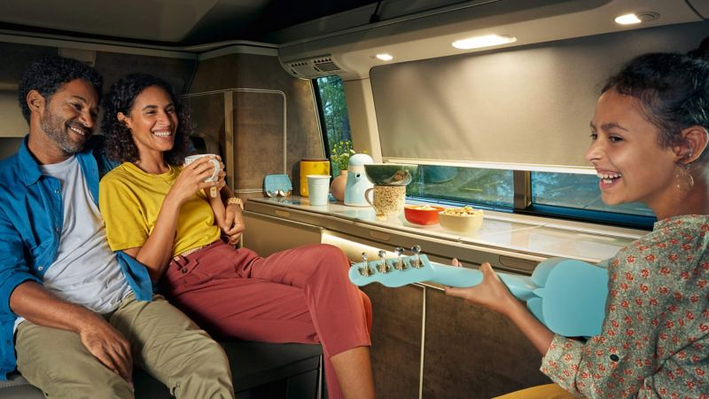 Young girl playing with family in VW California kitchen