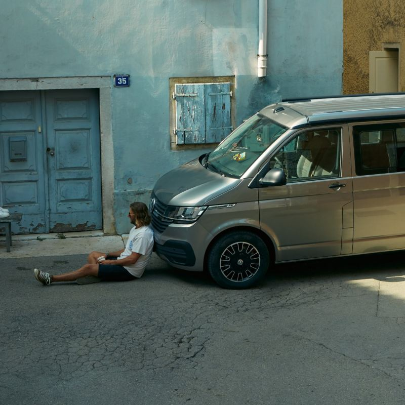 Two people sitting in the street with one of them leaning against a California Beach van