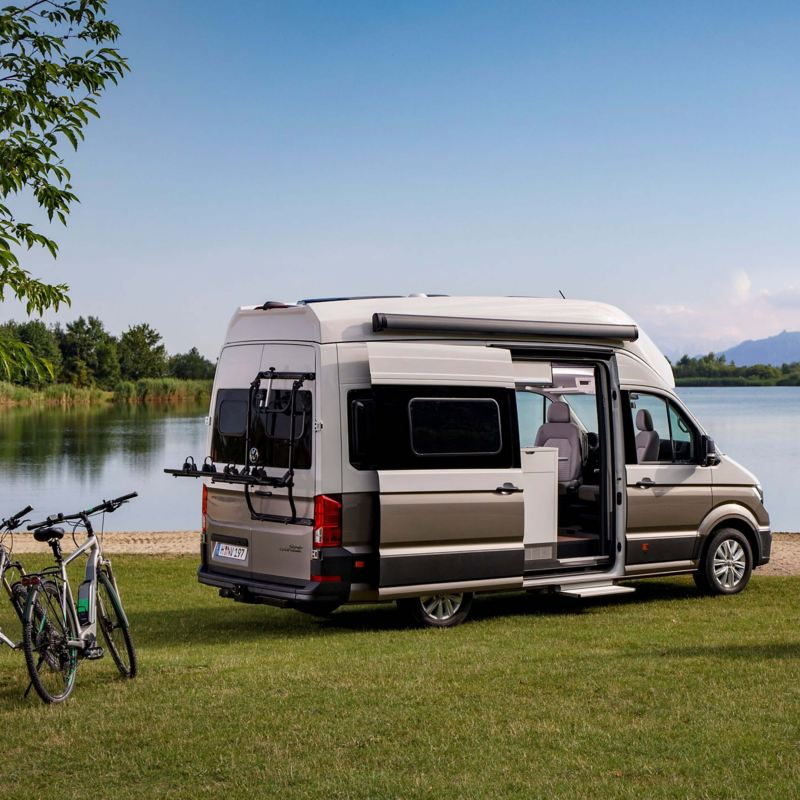 VW Grand California parked in meadow by lake