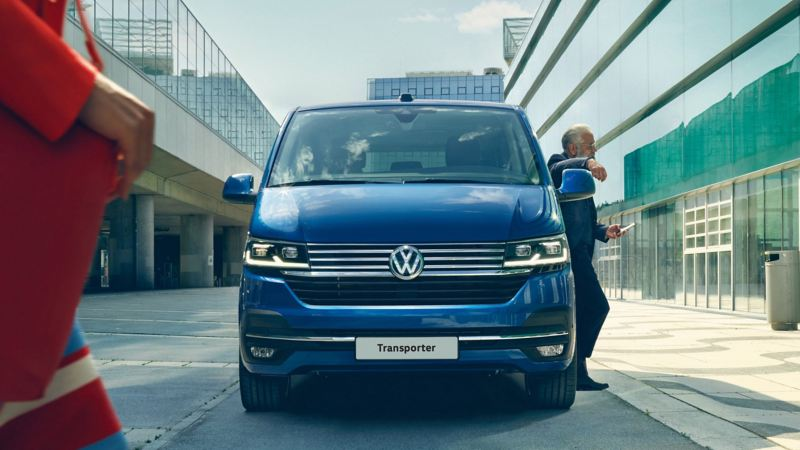 A man leaning against a blue Transporter Kombi
