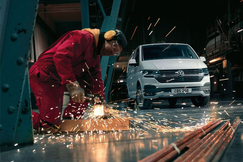 Worker cutting metal tube in front of new VW Transporter 6.1 van