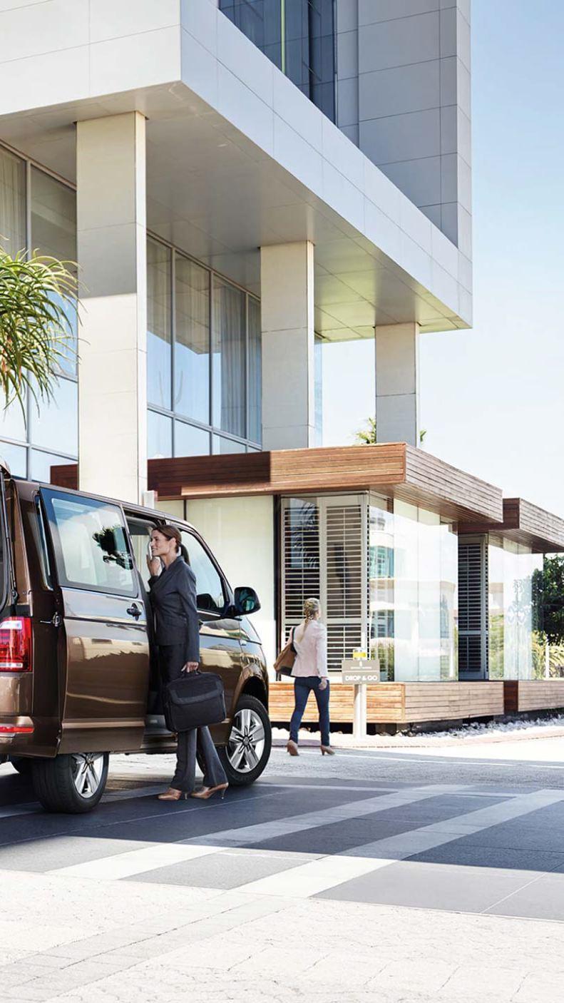 VW Transporter shuttle van outside hotel with passengers