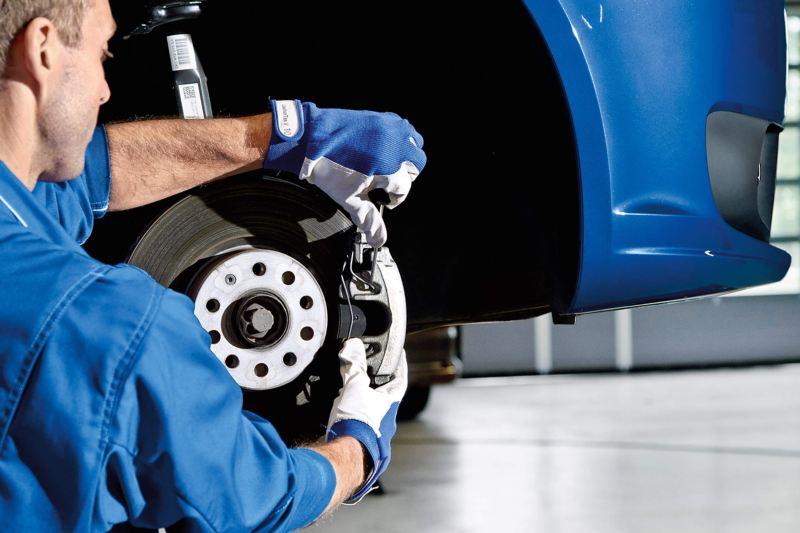 VW technician changing brake pad