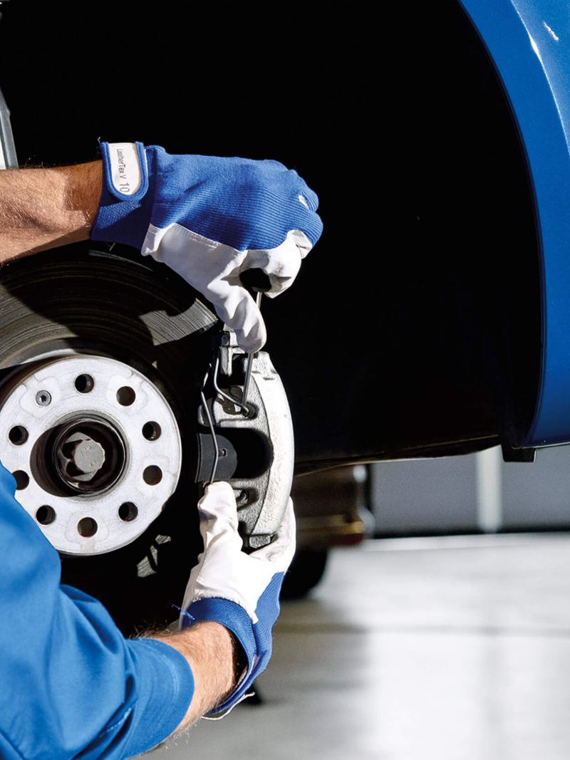 VW technician adjusting a wheel