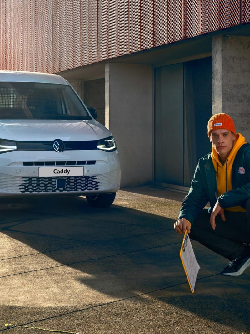Driver crouched in front of new VW Caddy 5 panel van with industrial background