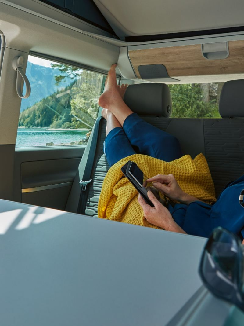 Woman reading on holiday in the back of a VW California 6.1 camper van in mountains