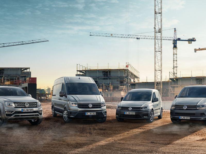 Verschiedene Volkswagen Nutzfahrzeuge stehen auf einer Großbaustelle.