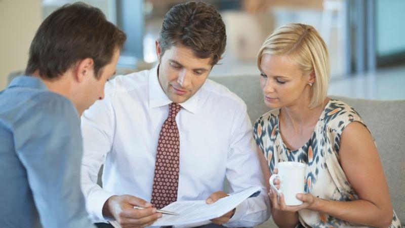 Zwei Männer und eine Frau blicken auf einen Zettel.