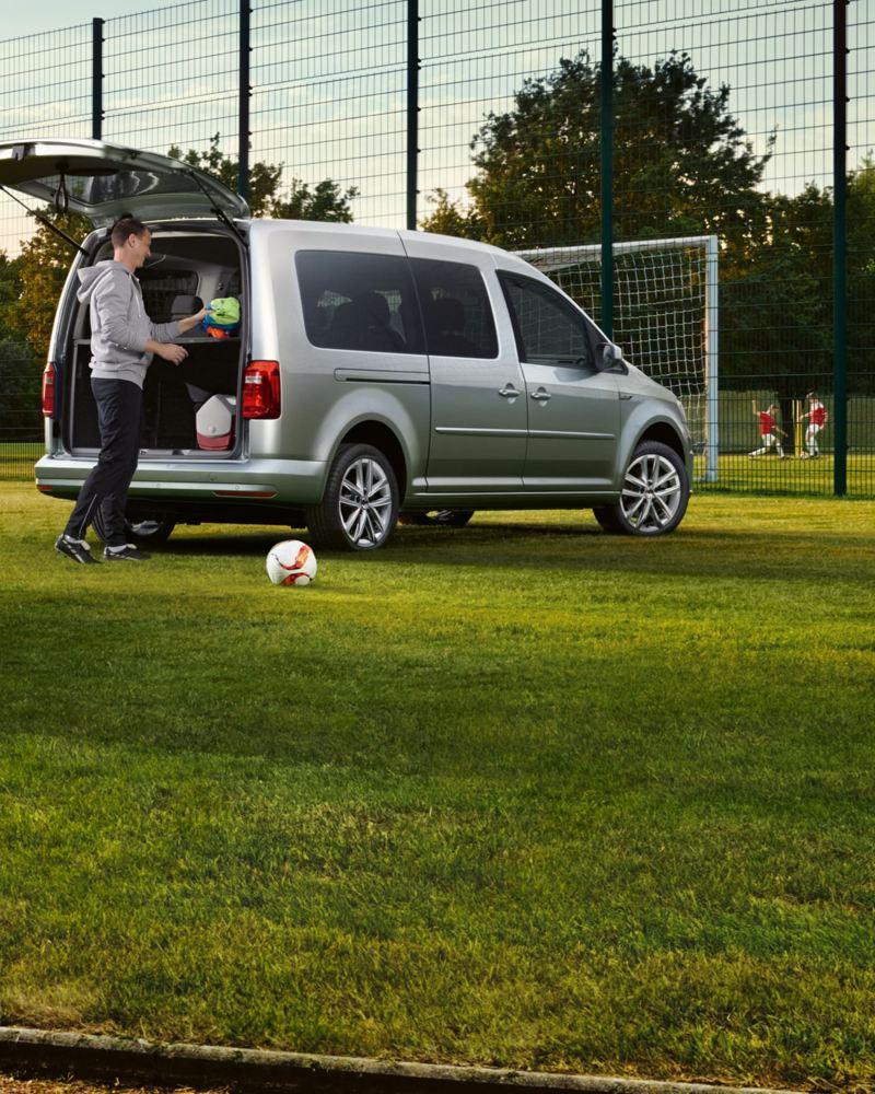 Ein Transporter und ein Caddy auf einer Wiese vor einem Fußballplatz.