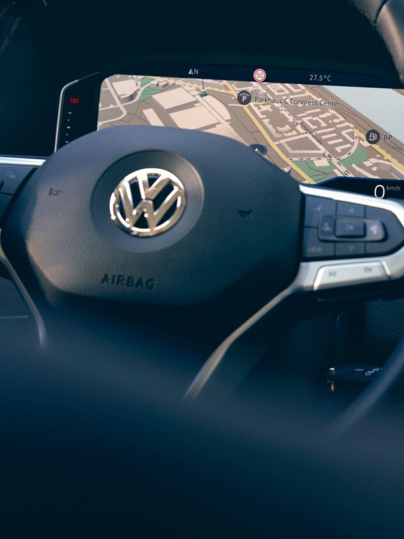 Une main manie un volant, la carte d'un système de navigation est affichée sur l'écran.
