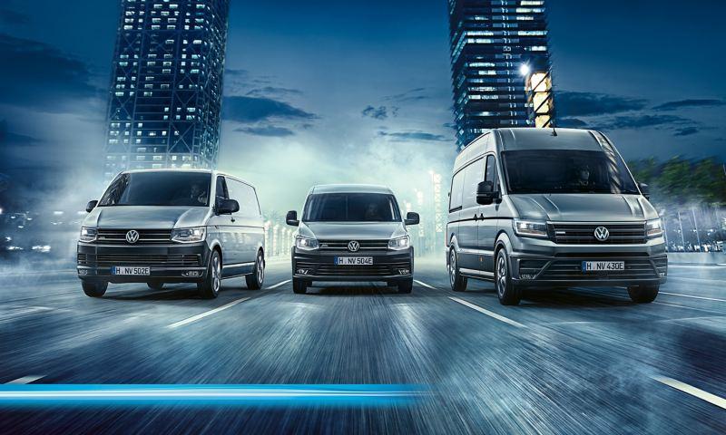 Gama modeli elektrycznych Volkswagen Samochody Dostawcze. e-Transporter, e-Caddy, e-Crafter dynamicznie przejeżdżają przez miasto.