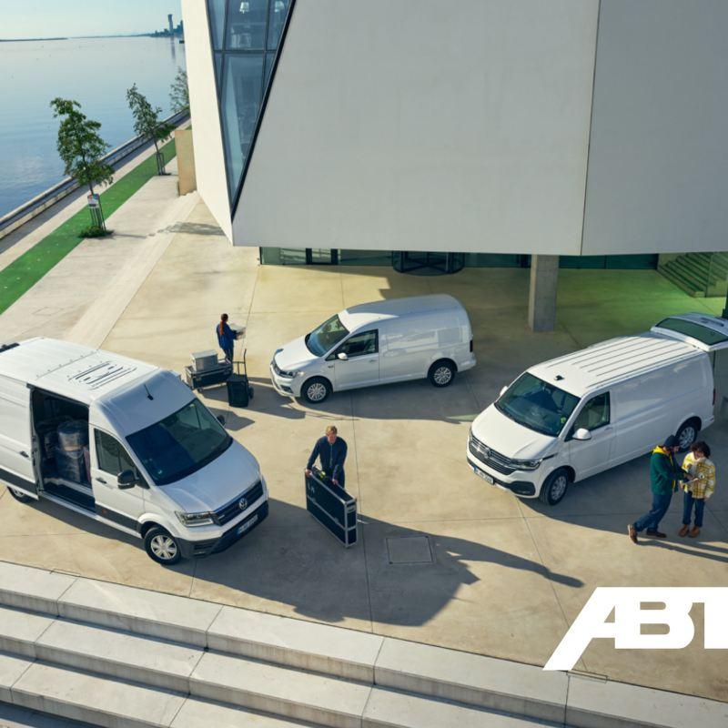 Der Volkswagen e-Crafter, ABT e-Transporter und ABT e-Caddy parken auf einem Platz vor einem Gebäudekomplex und werden entladen.