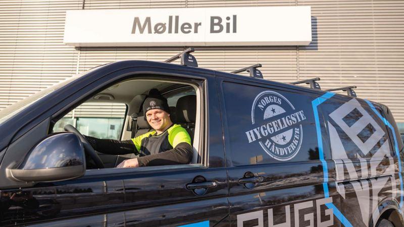 Bildet viser vinneren Alexander Nygaard-Andersen av kåringen Norges Hyggeligste Håndverker for 2020 som sitter i en ny Volkswagen Transporter varebil