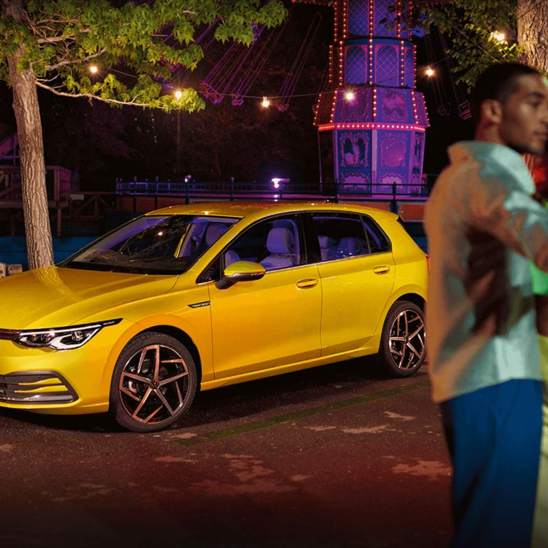 Vista lateral de VW Golf na estrada, um casal está à sua frente a tirar uma selfie