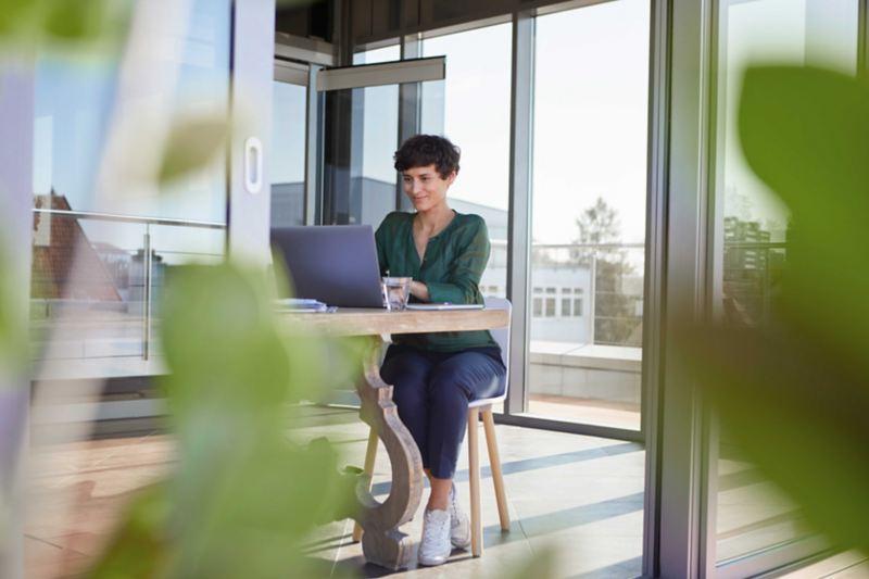 Eine Frau sitzt an einem Holztisch vor ihrem Laptop