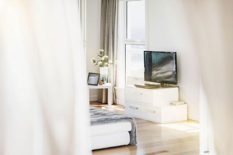 Appartamento con mobili bianchi e televisore a schermo piatto