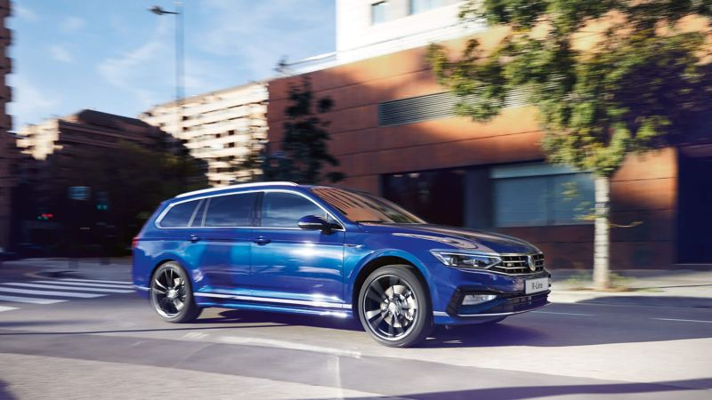 A blue Volkswagen Passat Estate, driving down a tree-lined city street.