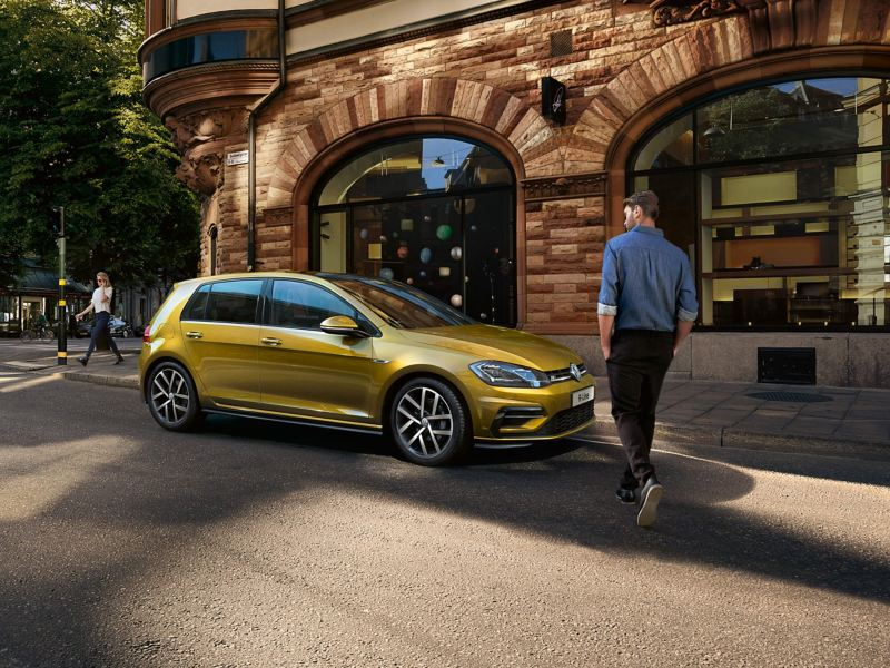 Man walking towards a yellow Volkswagen Golf, in a city street.