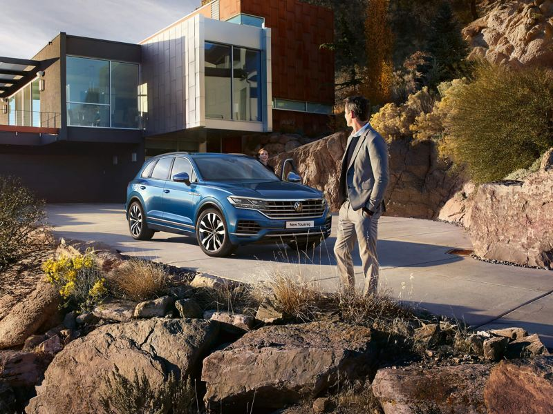 A man turning back to his partner, in a blue Volkswagen Touareg.