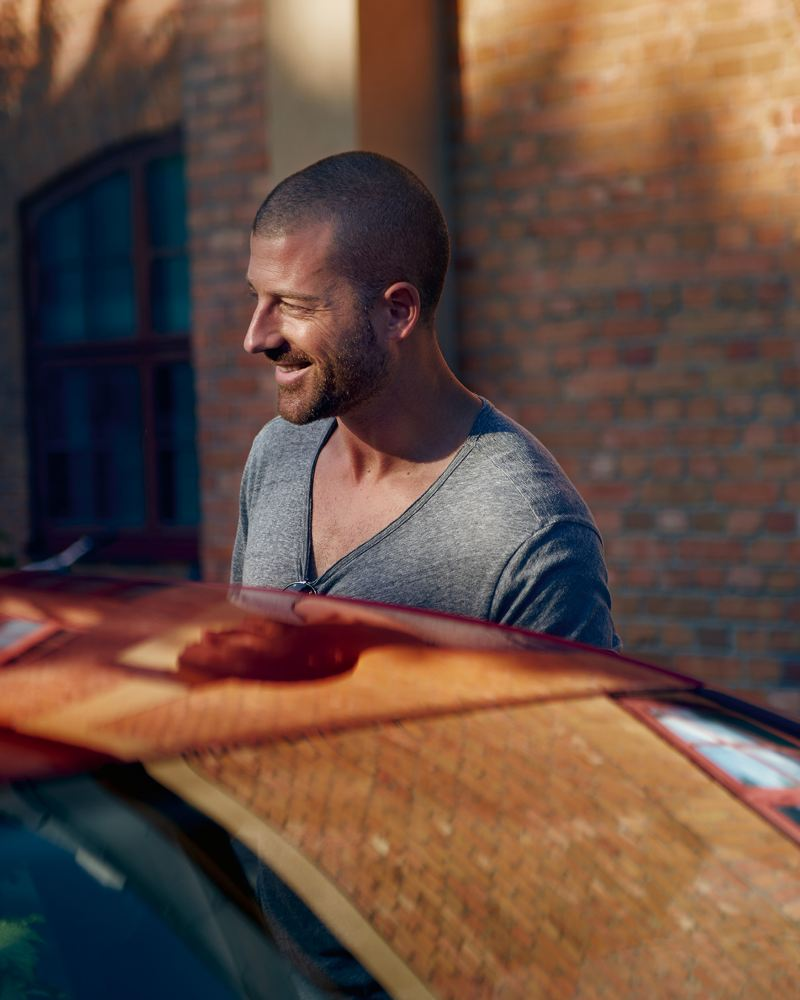 A man smiling next to a white Volkswagen e-Golf.
