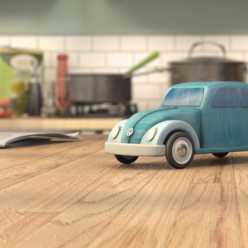 A small green toy Volkswagen Beetle, on a kitchen work surface.