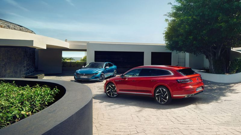 A blue and a red Volkswagen Arteon parked outside a house