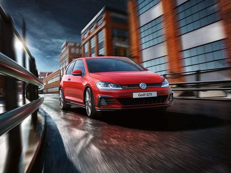 A red Volkswagen Golf GTI driving through an industrial city street at dawn.