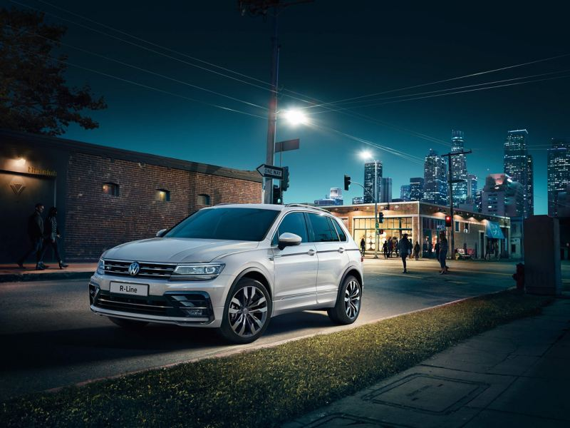 A grey Volkswagen Tiguan driving through an industrial city street at dawn.