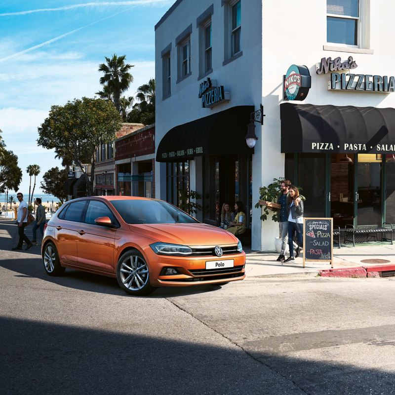 An orange Polo parked on the street in front of a restaurant