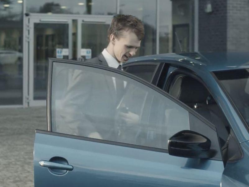 Man in suit opening a Volkswagen car door