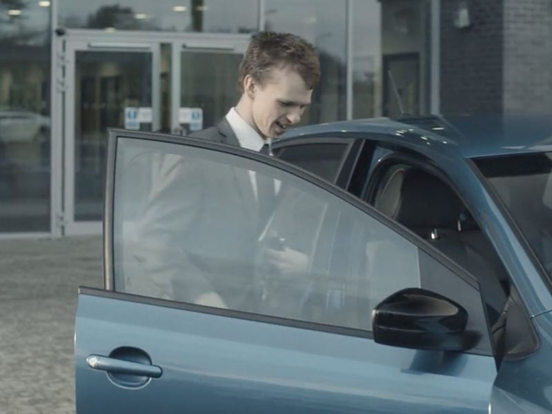 Man in suit opening a Volkswagen car door