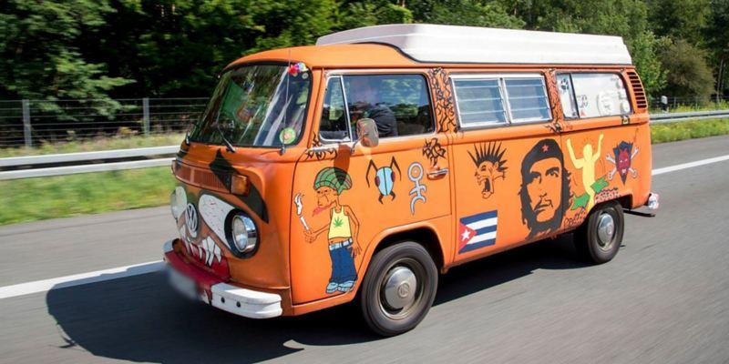 Ein orangener, bemalter Bulli fährt eine Straße entlang.