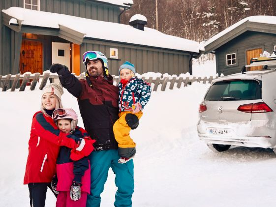 family infront of a house and the e-Golf with snowboard holder