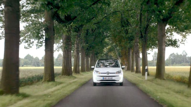 Vue frontale de la e-up! sur une route nationale bordée d'arbres