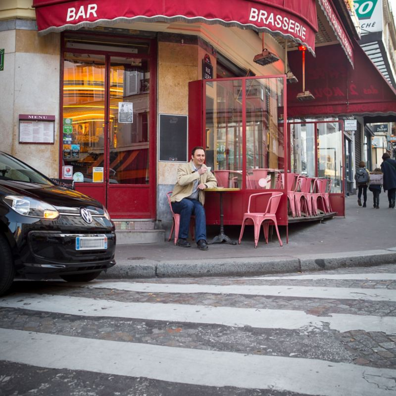 Alexandre Marie sitting in a café with his e-up! is parked next to him
