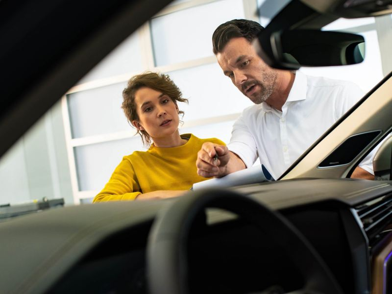 Man and woman talking about a car