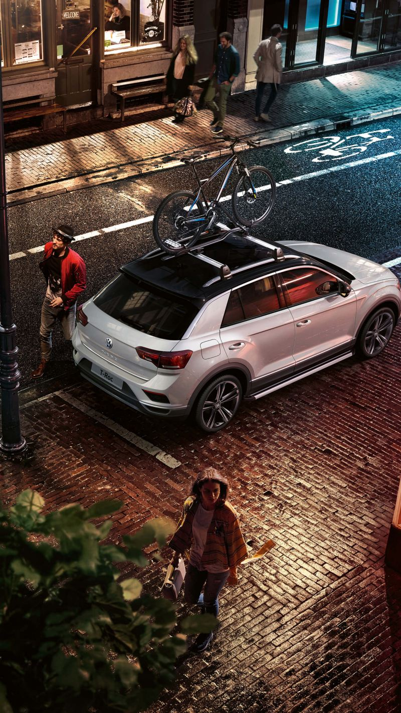 Volkswagen car with bicycle holder parked in street