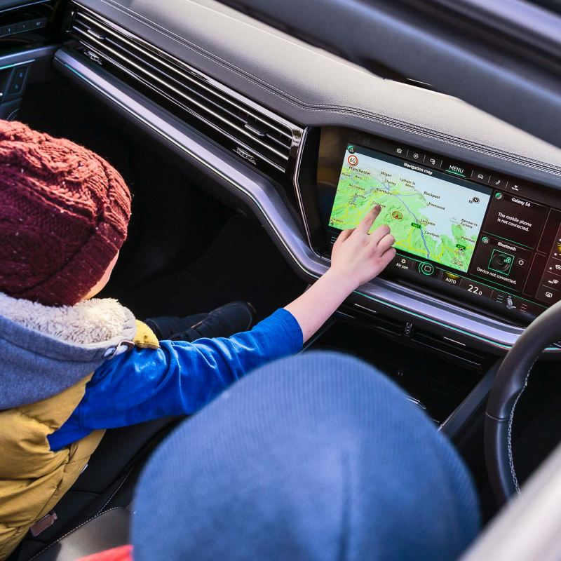 A child touching a car touch screen