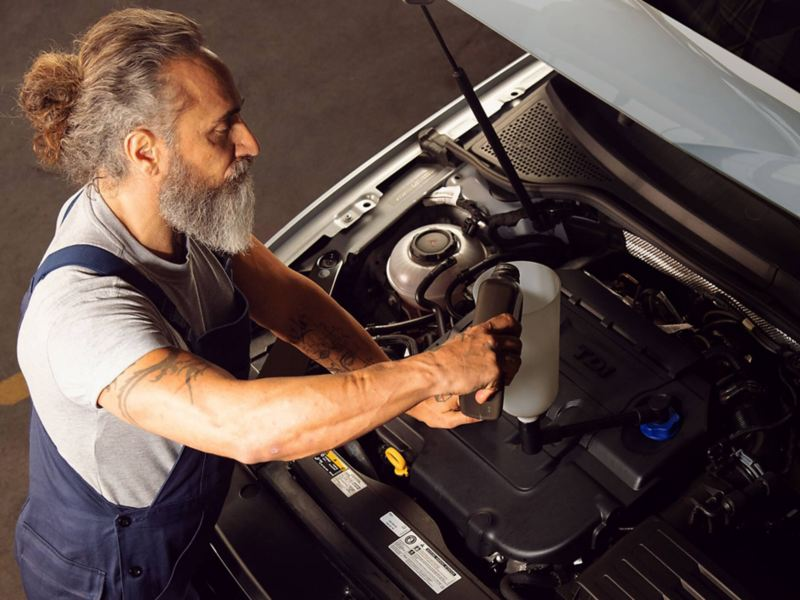Mechanic pouring oil into the car engine