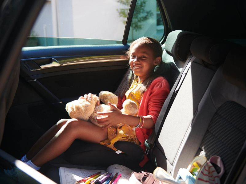 A little girl sitting in the back seat of a Volkswagen car