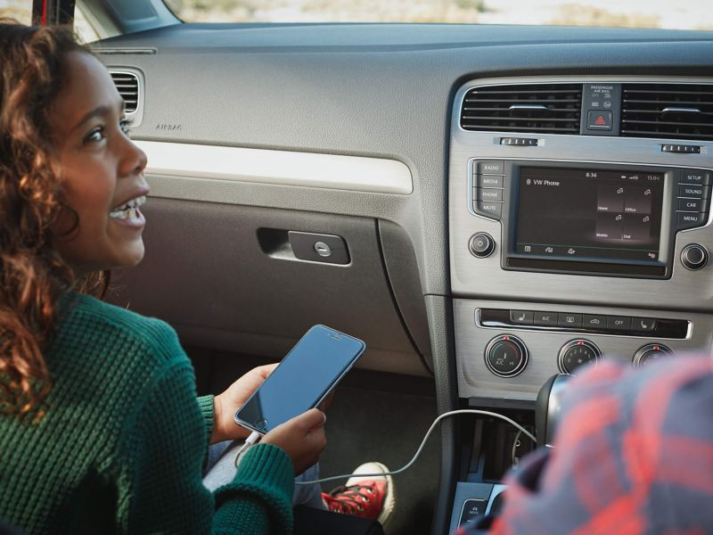 Female smiling on a phone in the car