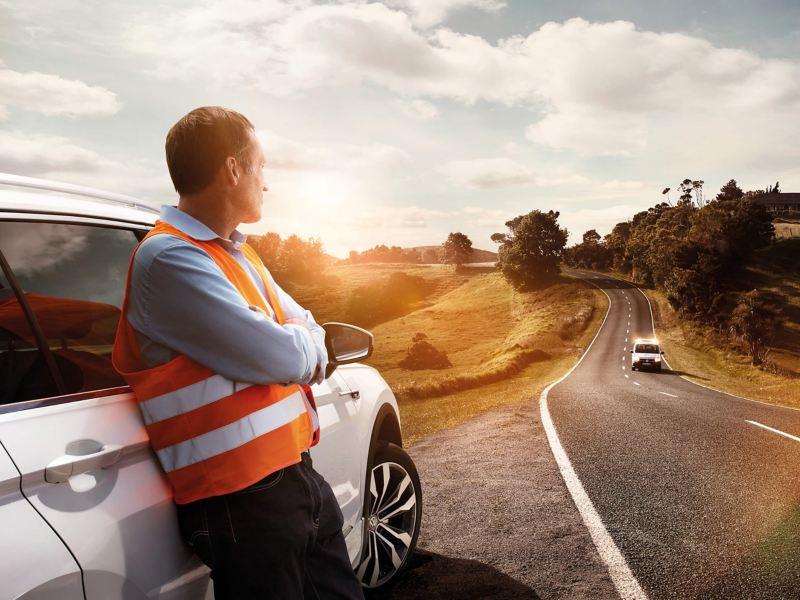 A man wearing a high viz waistcoat leaning against a car on a roadside