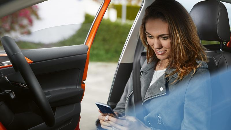 Woman using a smartphone in a Volkswagen car