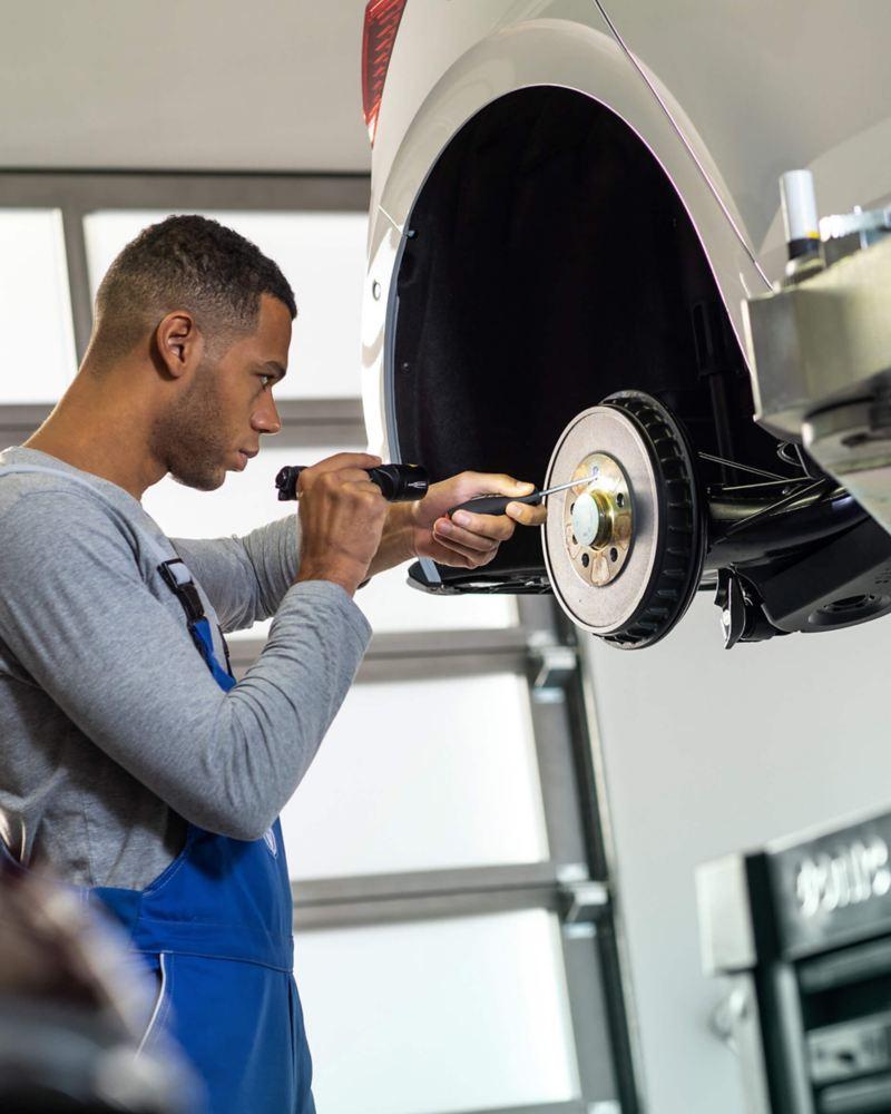 Technician servicing a Volkswagen vehicle.