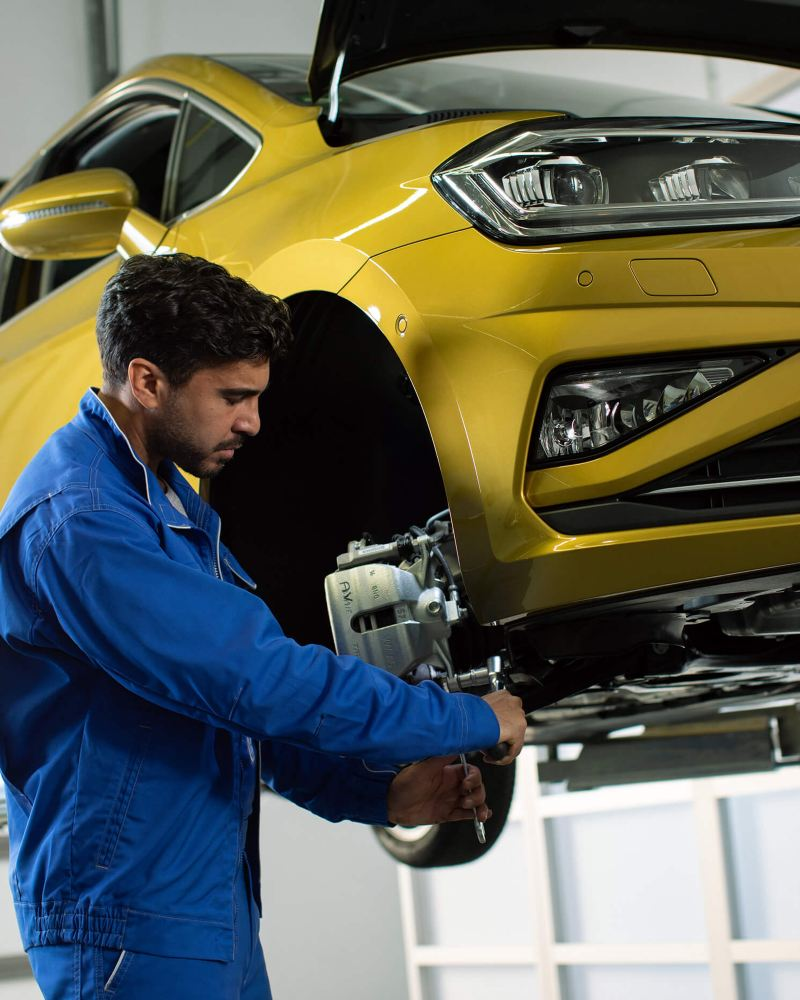 A Volkswagen technician servicing a car