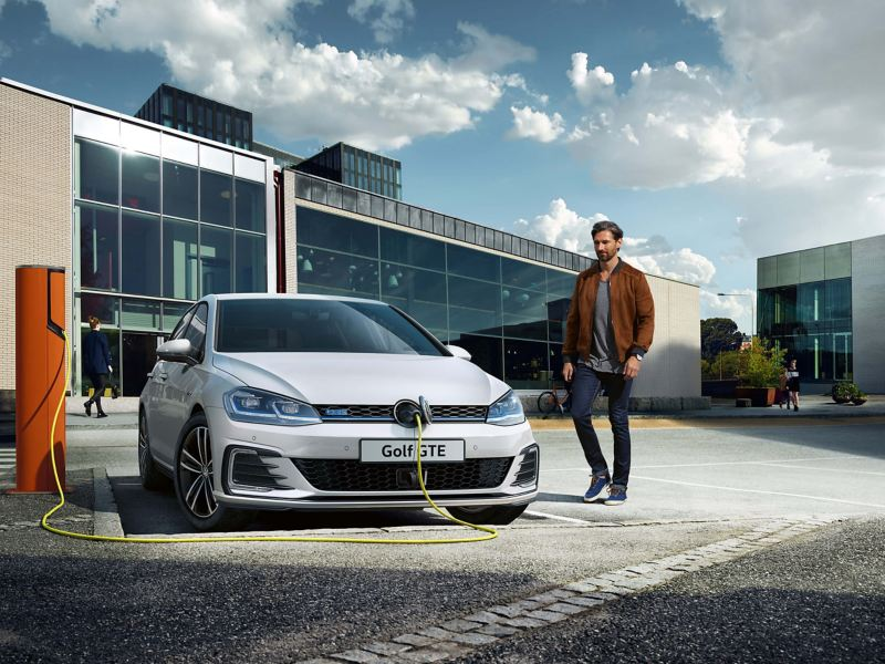 A man charging his Volkswagen Golf GTE electric vehicle in front of a building